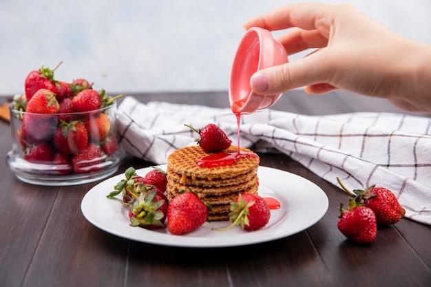 Vista frontal da mão derramando xarope de morango da tigela para biscoitos waffle e tigela de morango na superfície de madeira