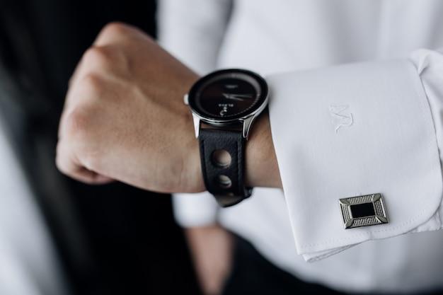 Vista frontal da mão do homem com elegante relógio e manga