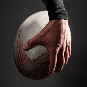 Vista frontal da mão do jogador de rugby segurando uma bola