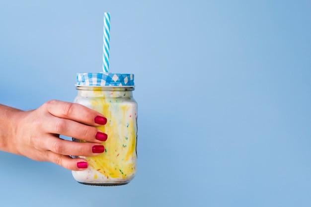 Vista frontal da mão e milk-shake em fundo azul com espaço de cópia