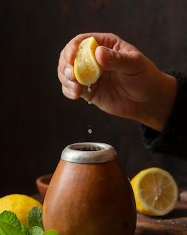 Vista frontal da mão espremendo limão sobre o chá