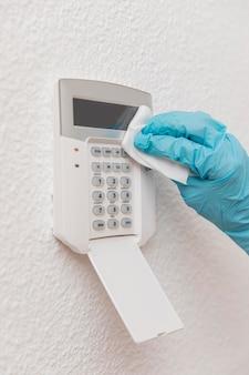 Vista frontal da mão que desinfecta o dispositivo doméstico
