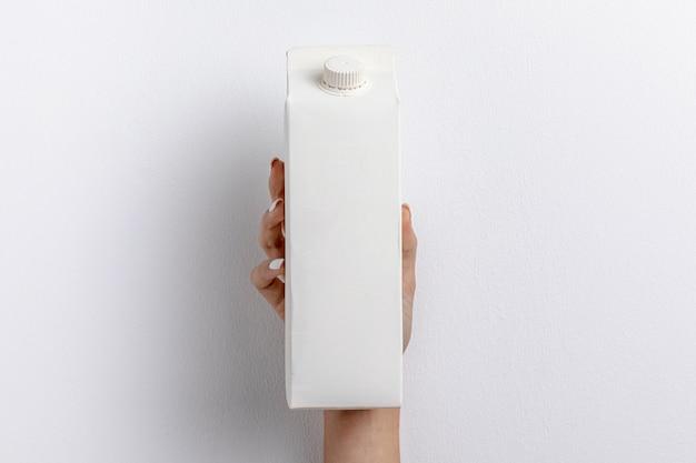 Vista frontal da mão segurando a caixa de leite simples