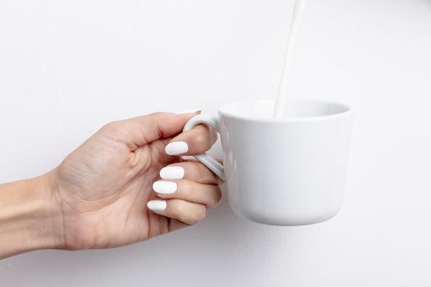 Vista frontal da mão segurando a caneca com leite
