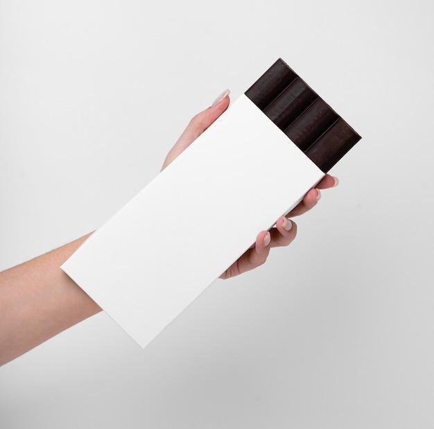 Vista frontal da mão segurando a pastilha de chocolate com embalagem e espaço de cópia