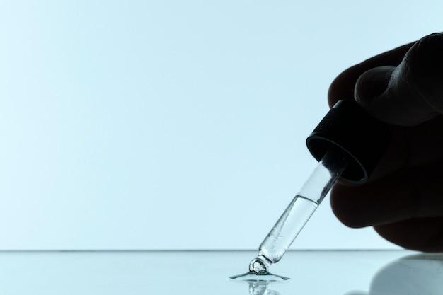 Vista frontal da mão segurando a pipeta com líquido e espaço de cópia
