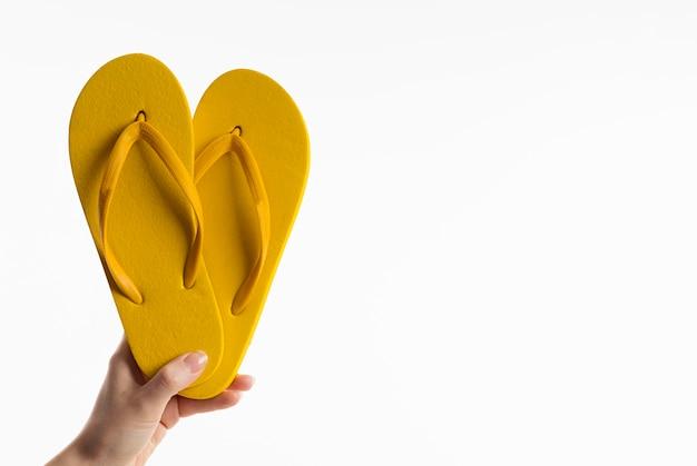 Vista frontal da mão segurando chinelos