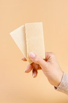 Vista frontal da mão segurando dois pedaços de bolacha