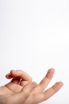 Vista frontal da mão segurando lentes de contato nos dedos