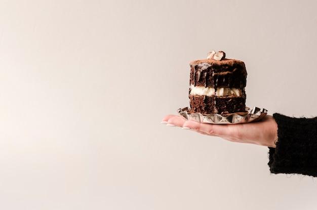 Vista frontal da mão segurando o bolo com espaço de cópia