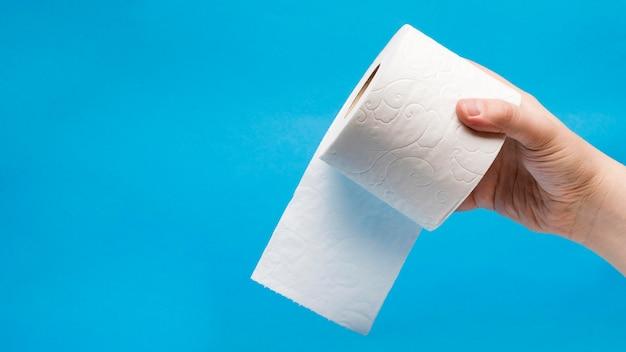 Vista frontal da mão segurando o papel higiênico