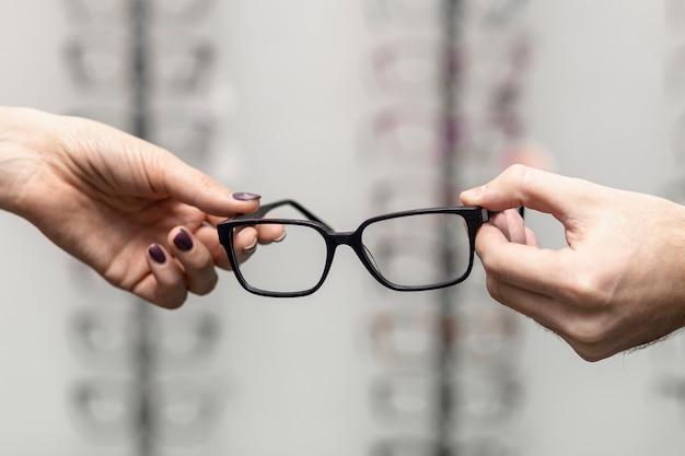 Vista frontal da mão segurando o par de óculos