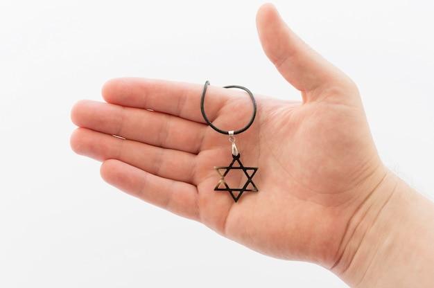 Vista frontal da mão segurando o pingente de estrela de david