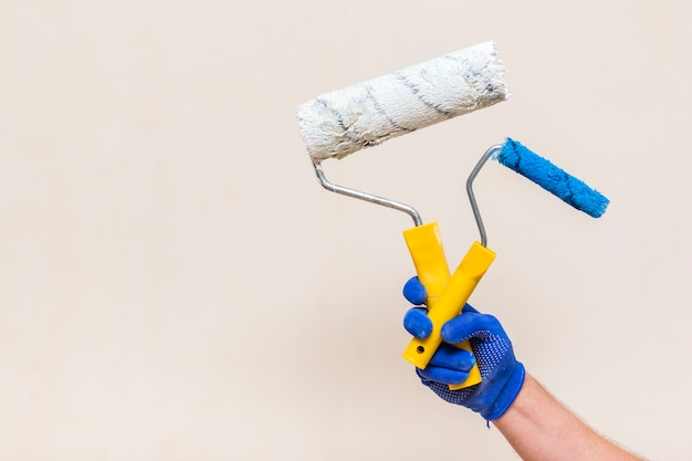 Vista frontal da mão segurando os rolos de pintura