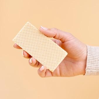 Vista frontal da mão segurando um pedaço de bolacha