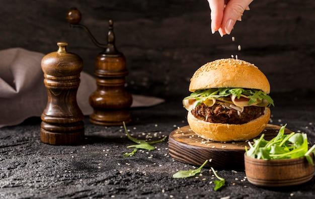 Vista frontal da mão servindo sementes de gergelim sobre hambúrguer de carne com salada e bacon