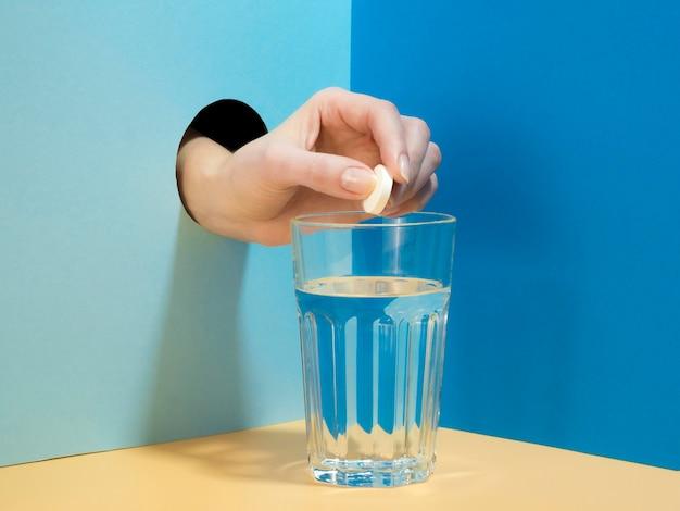 Vista frontal da mão soltando comprimido efervescente em copo de água