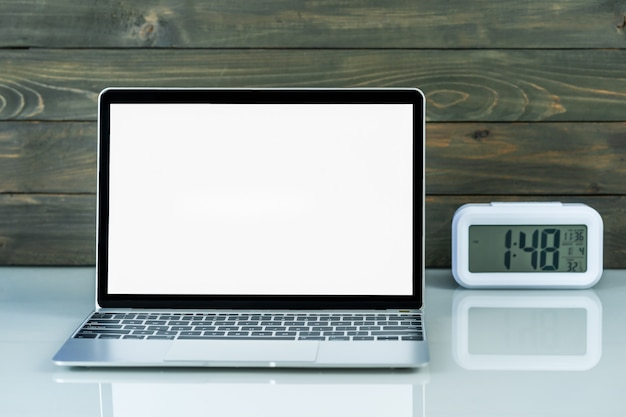 Vista frontal da maquete de laptop e despertador com fundo de madeira na mesa de trabalho