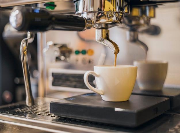 Vista frontal da máquina de café fazendo café