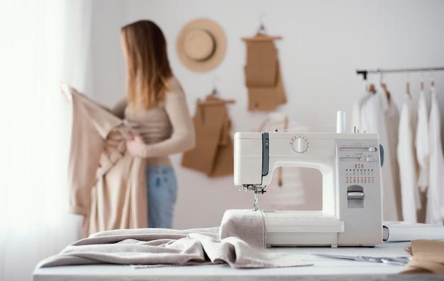 Vista frontal da máquina de costura na mesa do estúdio de alfaiataria