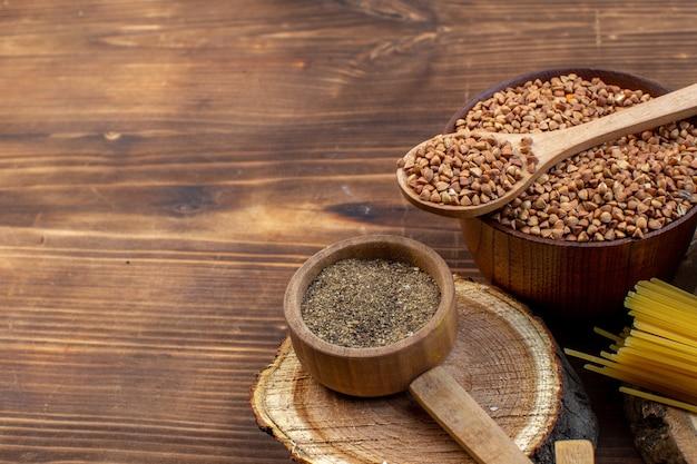 Vista frontal da massa crua com trigo sarraceno e lentilhas na superfície marrom