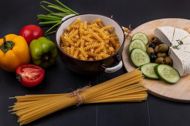 Vista frontal da massa crua em uma panela com espaguete cru e pimentão, queijo feta, pepinos e azeitonas em um suporte sobre um fundo preto