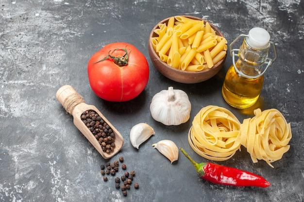 Vista frontal da massa italiana crua com ovos, tomate e óleo sobre fundo cinza claro