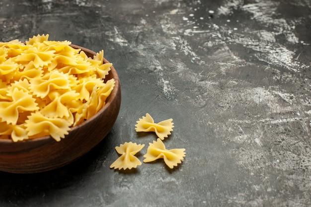 Vista frontal da massa italiana crua dentro do prato na cor cinza-escuro massa de refeição muitos alimentos espaço livre