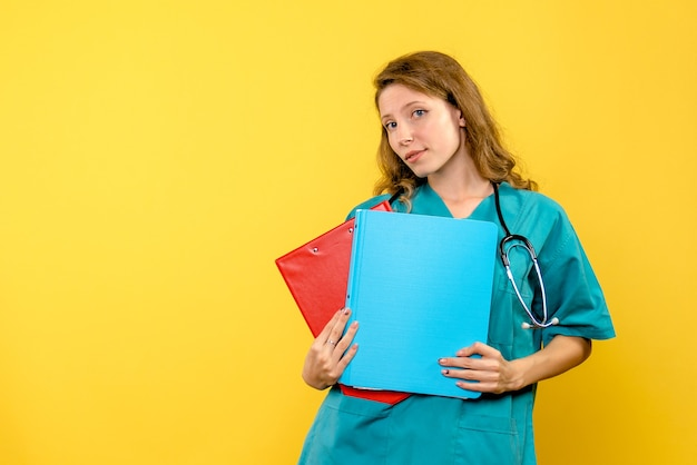 Vista frontal da médica com análises na parede amarela