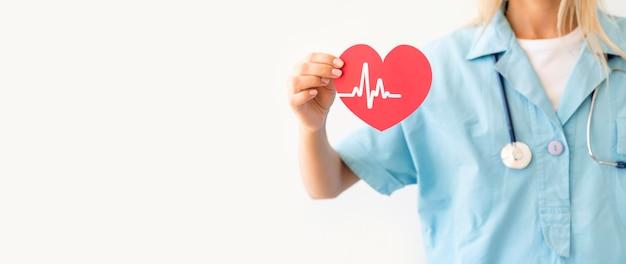 Vista frontal da médica com estetoscópio segurando um coração de papel com batimentos cardíacos