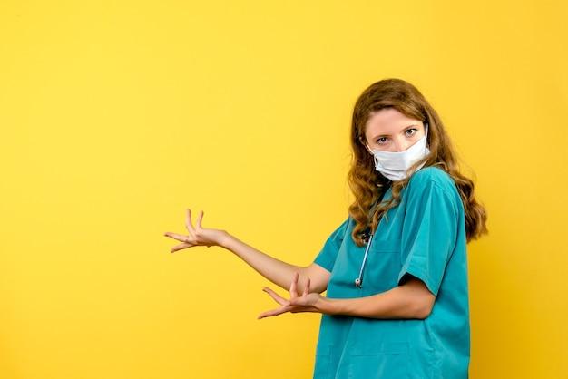 Vista frontal da médica com máscara na parede amarela Foto gratuita