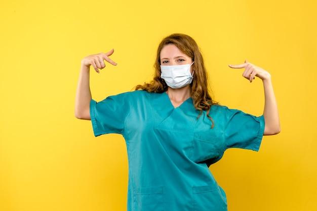 Vista frontal da médica com máscara na parede amarela