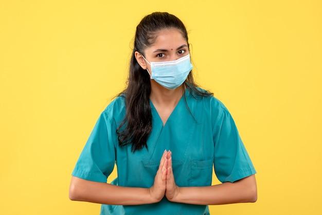 Vista frontal da médica com máscara unindo as mãos em pé na parede amarela