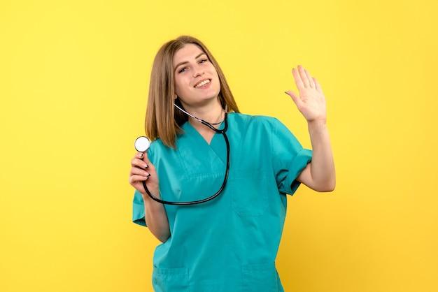 Vista frontal da médica com tonômetro na parede amarela