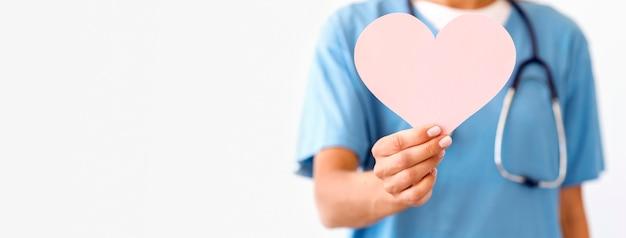 Vista frontal da médica desfocada segurando um coração de papel
