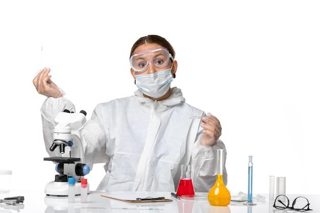 Vista frontal da médica em traje de proteção e com máscara trabalhando com soluções em fundo branco vírus covid pandêmico coronavírus