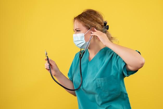 Vista frontal da médica em traje médico e máscara com estetoscópio na parede amarela