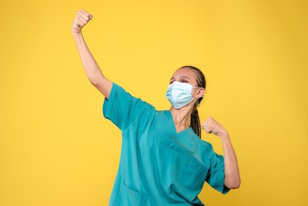 Vista frontal da médica em traje médico e máscara estéril na parede amarela