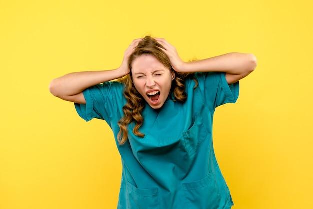 Vista frontal da médica gritando na parede amarela