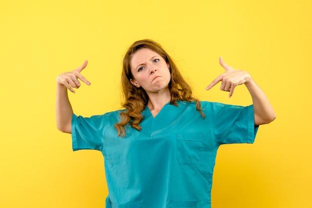 Vista frontal da médica na parede amarela