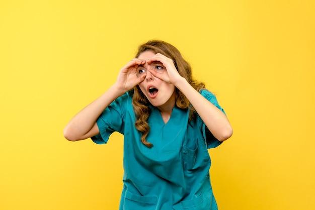 Vista frontal da médica olhando por entre os dedos na parede amarela