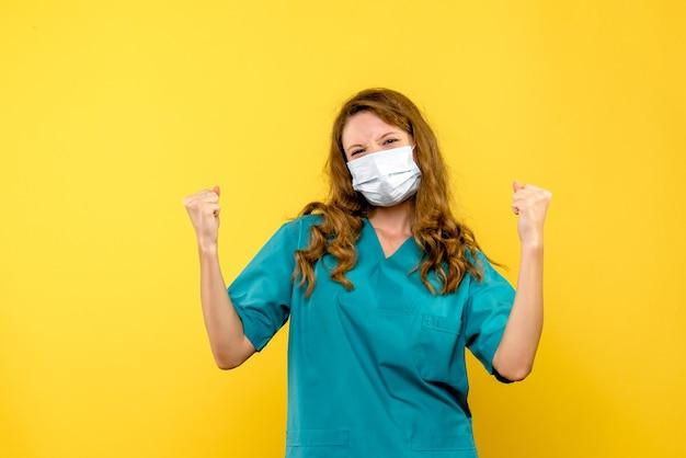Vista frontal da médica regozijando-se na máscara na parede amarela