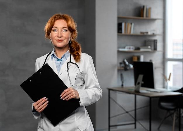 Vista frontal da médica segurando a prancheta com espaço de cópia
