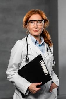 Vista frontal da médica segurando a prancheta e usando óculos