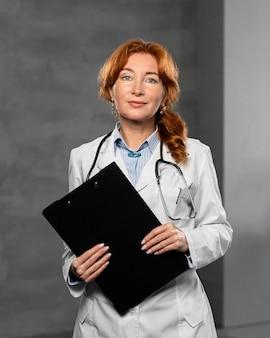 Vista frontal da médica segurando a prancheta