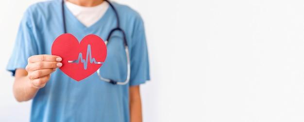 Vista frontal da médica segurando um coração de papel com espaço de cópia
