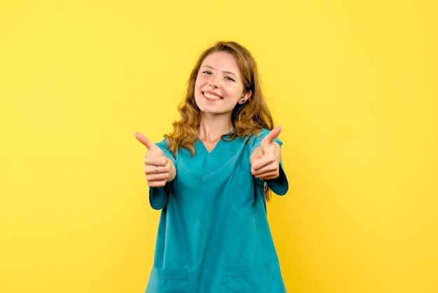 Vista frontal da médica sorrindo na parede amarela