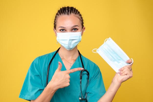 Vista frontal da médica usando máscara e segurando outra, vírus hospital pandêmico covid-19 enfermeira médica