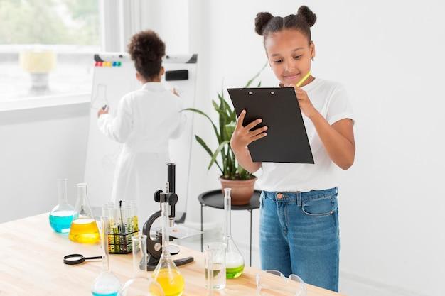 Vista frontal da menina ao lado da mesa com poções segurando o bloco de notas