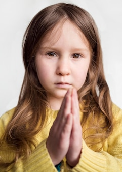 Vista frontal da menina bonitinha rezando